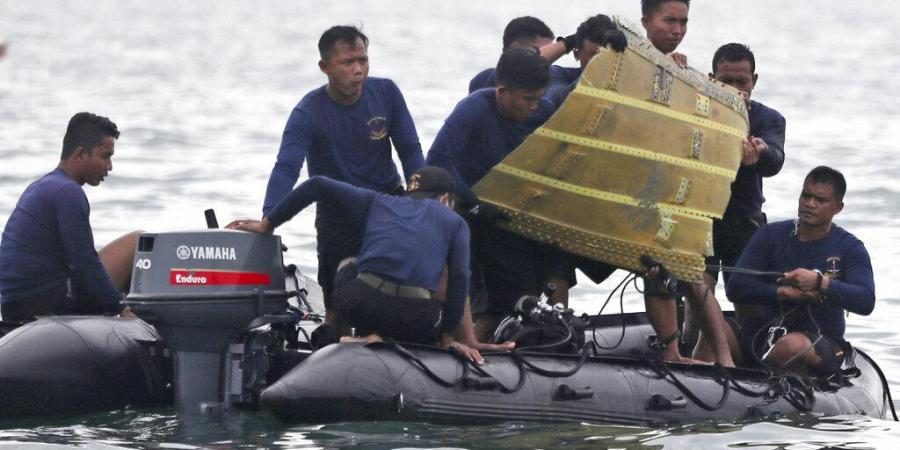 Indonesian Navy divers pull out a part of an airplane out of the water during a search operation for a Sriwijaya Air passenger jet.